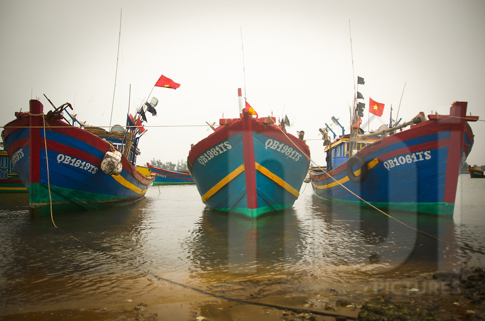 Colorful fishermen boat's bows are lined up and anchored to the shore. Dong Hoi, Quang Binh, Viet Nam. Asia. Vietnamese flags float on each boat.