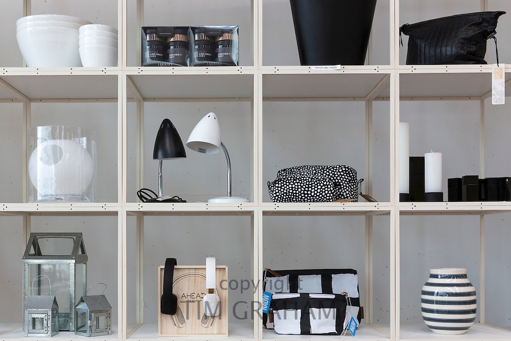 Monochrome shelf display of black and white gifts souvenirs lamps vases in shop at Arken Museum of Modern Art, Denmark