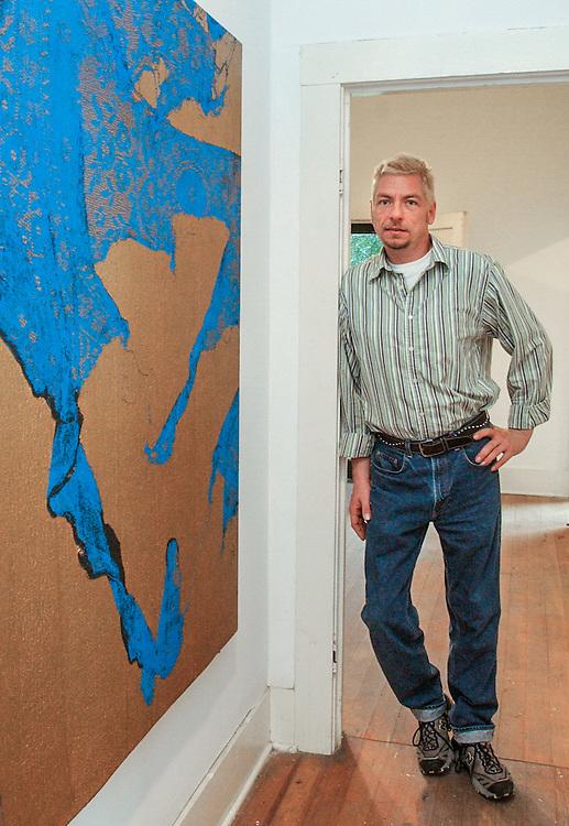 Sala Diaz' Chuck Ramirez stands next to a lace painting by Mark Flood.01/05/2016 175334 -- San Antonio, TX - © Copyright 2016 Mark C. Greenberg