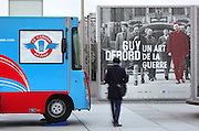 "Colorful food truck Le camion qui fume, a man walking seen from the back and another one, in red, looking camera through a poster of ""Guy Debord, Un art de la guerre"", exhibition at BNF Francois Mitterand, Avenue de France, 13th arrondissement, Paris, France. Picture by Manuel Cohen"