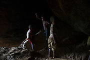 Maniq children play in the cave that they moved in to until the monsoon rains subside. After this they will return to the forest.<br /> <br /> Evidence suggests that the Maniq, a Negrito tribe of hunters and gatherers, have inhabited the Malay Peninsula for around 25,000 years. Today a population of approximately 350 maniq remain, marooned on a forest covered mountain range in Southern Thailand. Whilst some have left their traditional life forming small villages, the majority still live the way they have for millennia, moving around the forest following food sources. <br /> <br /> Quiet and reclusive they are little known even in Thailand itself but due to rapid deforestation they are finding it harder to survive on the forest alone and are slowly being forced to move to its peripheries closer to Thai communities.
