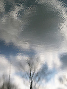 Clouds are reflected in the water of a pond in Flushing Meadows Corona Park.  A slight breeze gives the water a subtle rippled effect throughout the frame of the picture.