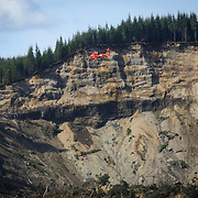 A U.S Coast Guard helicopter flies over the site of the Oso mudslide on Monday, March 31, 2014 near Darrington. Work continues in the debris field as workers try to account for victims of the disaster. (Joshua Trujillo, seattlepi.com)