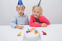 Happy siblings looking at birthday cake on table in house
