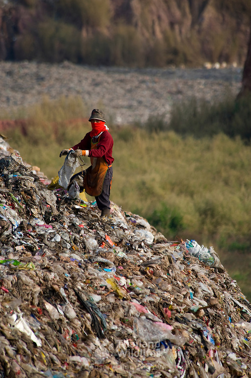 The poor hand sorting waste for recycling at a landfill site in Thailand.