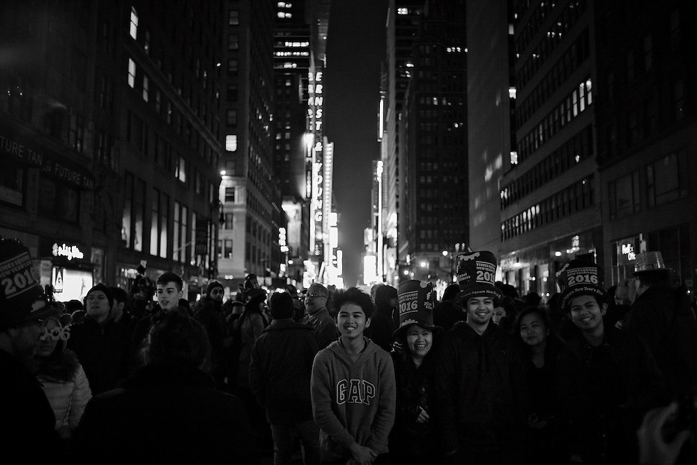 Peoplel on 7th Avenue at the back of the line of New Year's Eve celebrants south of Times Square, New York, NY, US
