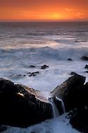 Sunset, coastal rocks and surf, Stillwater Cove Regional Park, Sonoma Coast, California