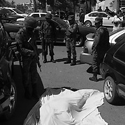 Surrounded by Mexican soldiers lies one of two men killed in a drug related assassination on a main street in broad daylight in Culiacan, Sinaloa which is the home turf of the Sinaloa Cartel in Mexico..(Credit Image: © Louie Palu/ZUMA Press).March 2012