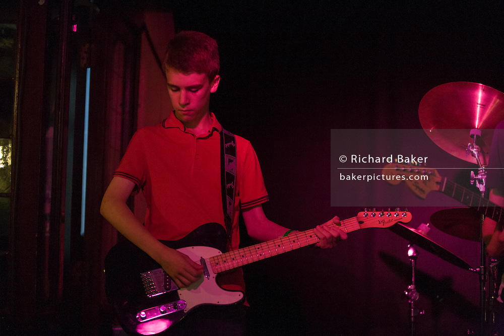 Schoolboy performs rock and roll song in a teenage band in a south London pub.