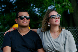 The Schuylkill River is seen reflected in the shades of a couple of spectators sitting on the river' banks as the Invisible River Festival takes place near the Strawberry Mansion Bridge, on Saturday. (Bastiaan Slabbers/for PhillyVoice)