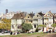 Mensen zitten bij Alamy Square voor de Paintes Ladies, een aantal Victoriaanse huizen. De Amerikaanse stad San Francisco aan de westkust is een van de grootste steden in Amerika en kenmerkt zich door de steile heuvels in de stad.<br /> <br /> People enjoy at Alamy Square with in front of the Painted Ladies, old Victorian houses. The US city of San Francisco on the west coast is one of the largest cities in America and is characterized by the steep hills in the city.