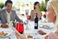Young woman holding wineglass sitting at table with friends