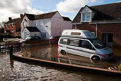 © London News Pictures. 24/02/2014. Moorland, UK. Flood water surrounding properties and cars in Moorland on the Somerset Levels, which continues to suffer from sever flooding. Photo credit: Jason Bryant/LNP
