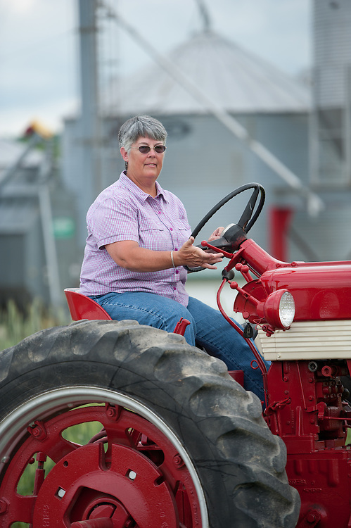 Woman farmer riding tractor in front of farm land in front of barns and silos