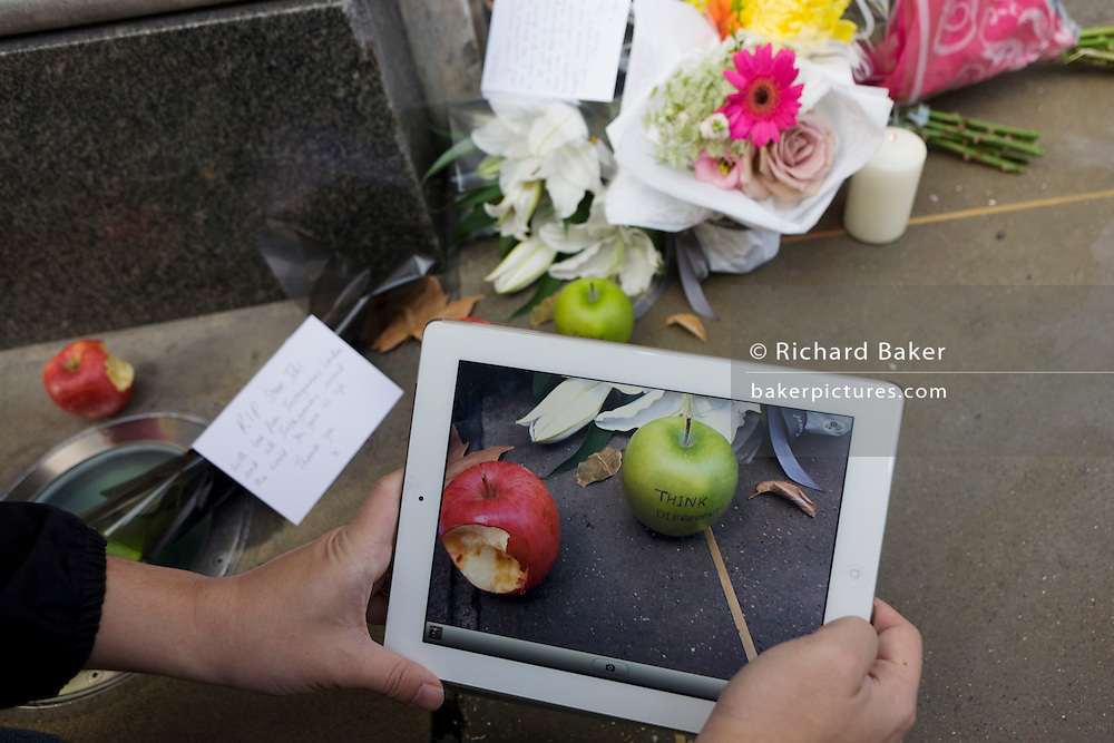 An Apple fan uses an iPad2 to photograph the makeshift shrine, where Londoners commemorate Apple's creator Steve Jobs the morning after hearing of his death overnight from pancreatic cancer  at the age of 56 on the 6th Oct 2011. This Apple Store in the capital's Regent's Street was the first to be built in Europe and serves as a flagship outlet for the stylish brand of computer accessories that were largely the brainchild of Jobs who started the company as a student in 1977.