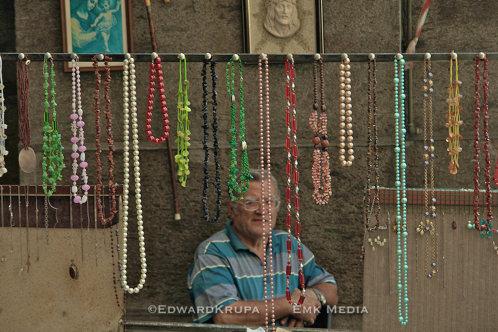 Street merchant selling costume jewelry in a market in Naples, Italy.