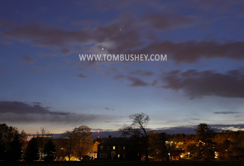 Middletown, New York - The crescent moon and Venus, to the upper right of the moon, shine in the night sky over suburban houses on April 24, 2012.