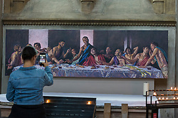 © Licensed to London News Pictures. 04/07/2020. ST ALBANS, UK.  A visitor views a version of the Last Supper, with Jesus as a black man, at St Albans Cathedral in support of Black Lives Matter.  The 8ft 8in-high (2.6m) high-resolution print of Lorna May Wadsworth's version of Leonardo da Vinci's 15th century masterpiece is on display above the Altar of the Persecuted in the North Transept of the cathedral and shows Tafari Hinds, a Jamaican model, as Jesus The artwork is part of a prayer installation to mark the cathedral's reopening after coronavirus pandemic lockdown restrictions were eased by the UK government.  Photo credit: Stephen Chung/LNP