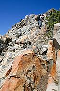 A backpacker scales a sheer cliff on Kendrick Peak, Yosemite National Park
