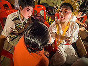 "06 DECEMBER 2015 - BANGKOK, THAILAND: Chinese opera performers put on their makeup before going on stage at the Ruby Goddess Shrine in the Dusit district of Bangkok. Chinese opera was once very popular in Thailand, where it is called ""Ngiew."" It is usually performed in the Teochew language. Millions of Chinese emigrated to Thailand (then Siam) in the 18th and 19th centuries and brought their culture with them. Recently the popularity of ngiew has faded as people turn to performances of opera on DVD or movies. There are about 30 Chinese opera troupes left in Bangkok and its environs. They are especially busy during Chinese New Year and Chinese holidays when they travel from Chinese temple to Chinese temple performing on stages they put up in streets near the temple, sometimes sleeping on hammocks they sling under their stage.     PHOTO BY JACK KURTZ"