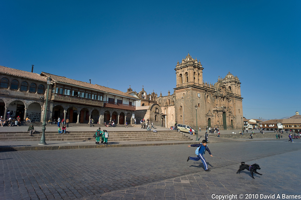 Boy running across street with dog, Cathedral, arcaded colonial buildings, Cusco, Peru