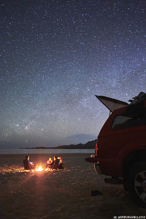 Car camping friends gather around a campfire on the beach below a night sky full of stars.