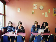 Four young men sitting at two tables in a cafe.