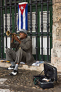 A street performer in Havana, Cuba's Plaza de Armas plays his trumpet for tourists and locals beneath the Cuban flag.
