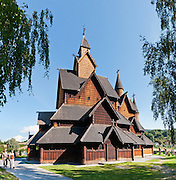 "A couple of people walk beside Heddal stave church, Norway's largest stave church. This triple nave stave church, which some call ""a Gothic cathedral in wood,"" was built in the early 13th century and restored in 1849-1851 and the 1950s. Heddal stavkirke is in Notodden municipality, Telemark County, Norway. Panorama stitched from 6 overlapping photos."