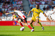 Paul Kalambayi (#30) of AFC Wimbledon looks to tackles Chris Maguire (#7) of Sunderland AFC during the EFL Sky Bet League 1 match between Sunderland and AFC Wimbledon at the Stadium Of Light, Sunderland, England on 24 August 2019.