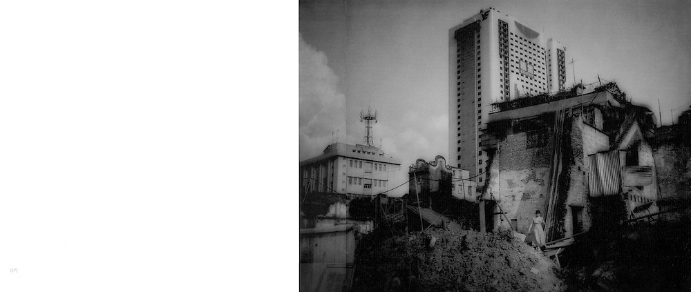 New highrises tower over a girl emerging from her soon to be demolished traditional house.  Guangzhou, China.  2000