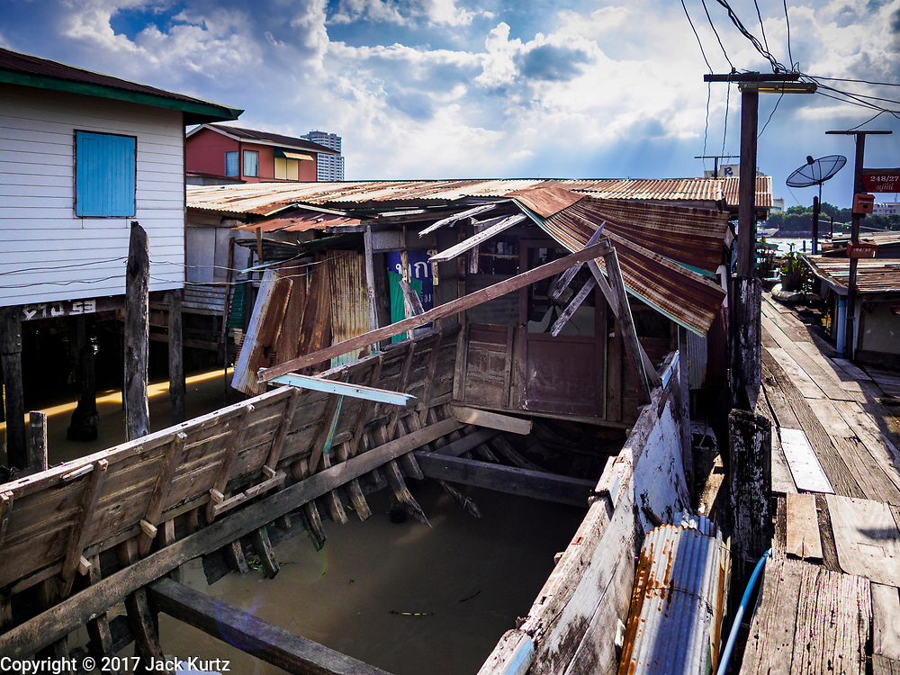 "20 JUNE 2017 - BANGKOK, THAILAND: An abandoned boat that used to be a home  in a community along the Chao Phraya River south of Krung Thon Bridge. This is one of the first parts of the riverbank that is scheduled to be redeveloped. The communities along the river don't know what's going to happen when the redevelopment starts. The Chao Phraya promenade is development project of parks, walkways and recreational areas on the Chao Phraya River between Pin Klao and Phra Nang Klao Bridges. The 14 kilometer long promenade will cost approximately 14 billion Baht (407 million US Dollars). The project involves the forced eviction of more than 200 communities of people who live along the river, a dozen riverfront  temples, several schools, and privately-owned piers on both sides of the Chao Phraya River. Construction is scheduled on the project is scheduled to start in early 2016. There has been very little public input on the planned redevelopment. The Thai government is also cracking down on homes built over the river, such homes are said to be in violation of the ""Navigation in Thai Waters Act."" Owners face fines and the possibility that their homes will be torn down.              PHOTO BY JACK KURTZ"