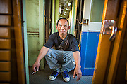 07 JANUARY 2013 - KANCHANABURI, THAILAND:  A man rests in the space between third class train cars on the train between Bangkok (Thonburi station) and Kanchanaburi. Thailand has a very advanced rail system and trains reach all parts of the country.    PHOTO BY JACK KURTZ