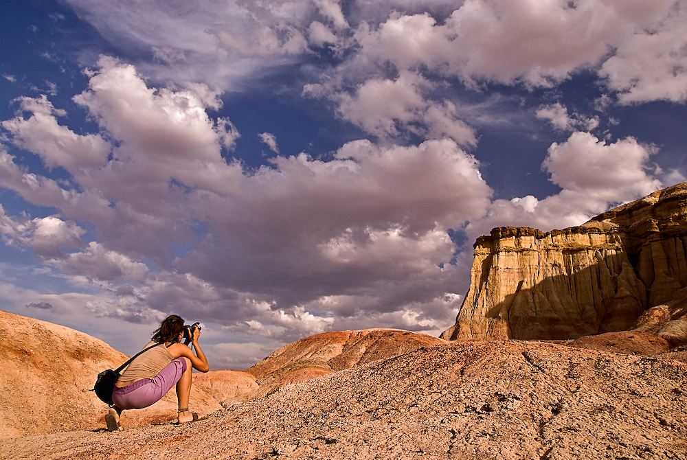 Woman taking a picture of a landscape of the Bayangovi area, Gobi desert, Mongolia.