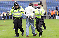 Photo: Rich Eaton.<br /> <br /> Oxford United v Leyton Orient. Coca Cola League 2. 06/05/2006.<br /> <br /> Oxford United fan is escorted from the pitch at the Kassam stadium after Oxford are relegated by Leyton Orient and both sets of fans invade the pitch