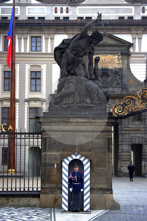 An honor guard stands at the main entrance to Prague Castle marked by statues of the Fighting Giants in Prague, Czech Republic. The castle, first constructed in the 10th century is the seat of government in the Czech Republic.