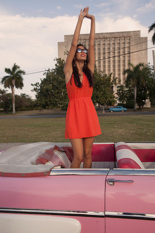 A young Cuban woman enjoys the sun standing up in a convertible at the Revolution Square in Havana, Cuba.