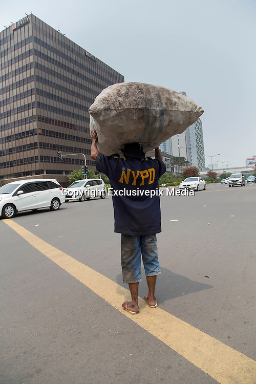Jakarta, Indonesia 17 January 2016 : <br /> <br /> A scavenger at thamrin street jakarta near the bombing site location. Jakarta back to normal again after the fatal attack at Starbuck Coffee at Thamrin Street. Peoples still visiting to the bombing site to take photos and condemn to the terrorist action.<br /> ©Exclusivepix Media