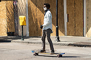 Charleston, United States. 31 May, 2020. A skateboard rides past boarded up shops along the King Street shopping district after a protest over the death of George Floyd, turned violent and destructive May 31, 2020 in Charleston, South Carolina. Floyd was choked to death by police in Minneapolis resulting in protests sweeping across the nation.  Credit: Richard Ellis/Alamy Live News