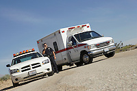 Police officer standing by police car and ambulance