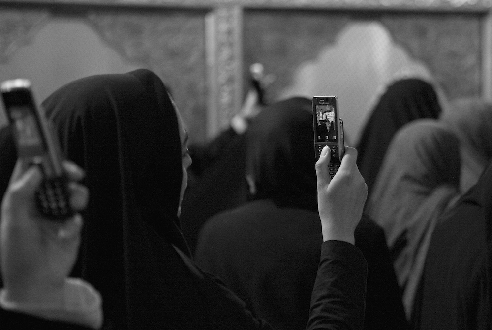 Women use cell phones to photograph tomb at the Sayyidah Ruqayya Mosque, Damascus