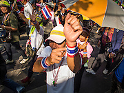 """05 JANUARY 2014 - BANGKOK, THAILAND:  Anti-government protestors waving Thai flags and wearing """"Long Live the King"""" headbands walk through Bangkok. Suthep Thaugsuband, leader of the anti-government protests in Bangkok, led the protestors on a march through the Chinatown district of Bangkok. Tens of thousands of people waving Thai flags and blowing whistles gridlocked what was already one of the most congested parts of the city. The march was intended to be a warm up to their plan by protestors to completely shut down Bangkok starting Jan. 13.    PHOTO BY JACK KURTZ"""