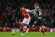Alex Oxlade-Chamberlain of Arsenal and Jack Colback of Newcastle United during the Barclays Premier League match at the Emirates Stadium, London<br /> Picture by David Horn/Focus Images Ltd +44 7545 970036<br /> 13/12/2014