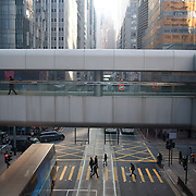 The view from a walkway in Central Hong of tall buildings made in glass and steel.