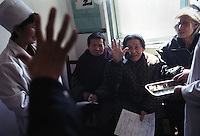 North Korea Eye Surgery Workshop. A patient is asked by nurses to hold up five fingers in postoperative examinations after her cataract surgery.