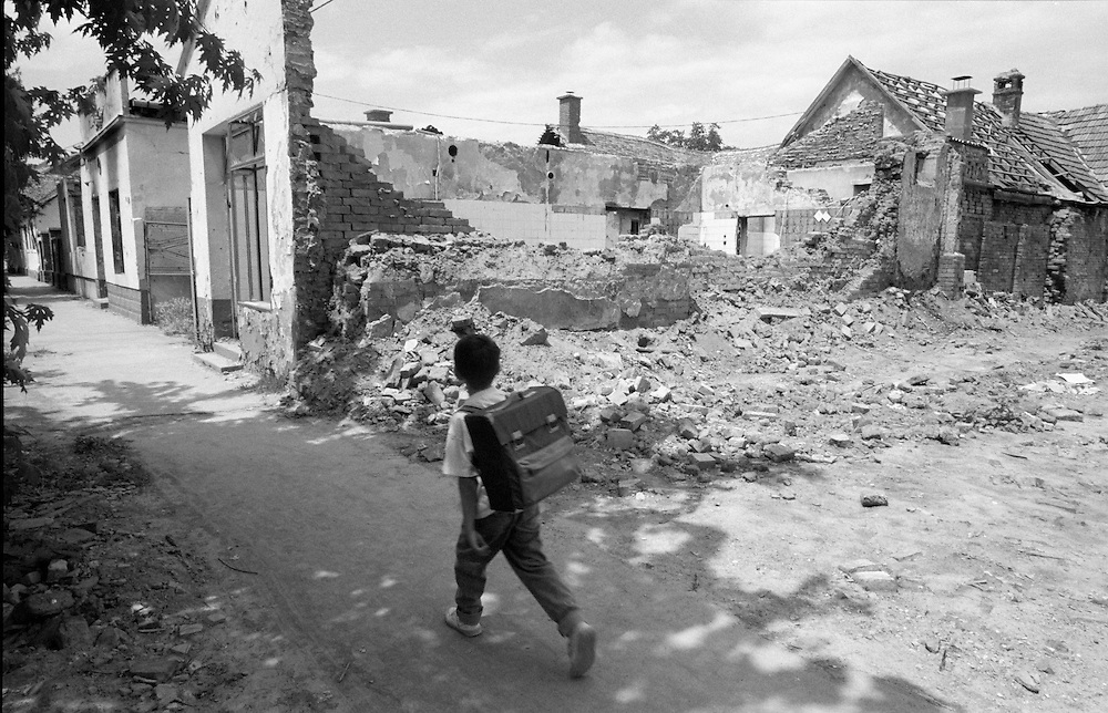A young boy walks home from school by the devastation in the war torn town of Nustar.