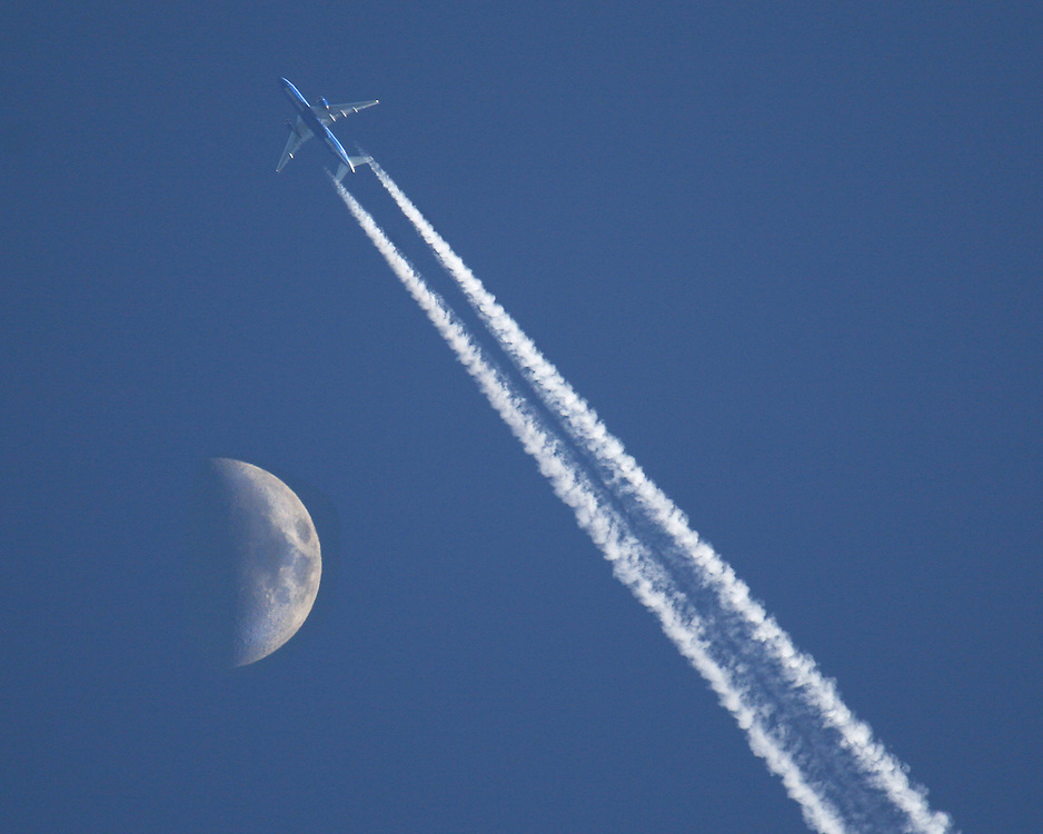 Photographed from my roof. A great place to wait for these shots. The planes with trails are passing well over landing and take off altitudes, and are a common site. Not so easy to get them though, in range of the moon.