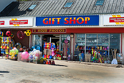 "A traditional Sea front Gift Shop with one of the rapidly disappearing ""1 Hour Photos"" signs displays its main products of Buckets Spades and Beach ball  on Cobble Landing at Filey North Yorkshire<br /> <br /> 21 May 2013<br /> Image © Paul David Drabble<br /> www.pauldaviddrabble.co.uk"