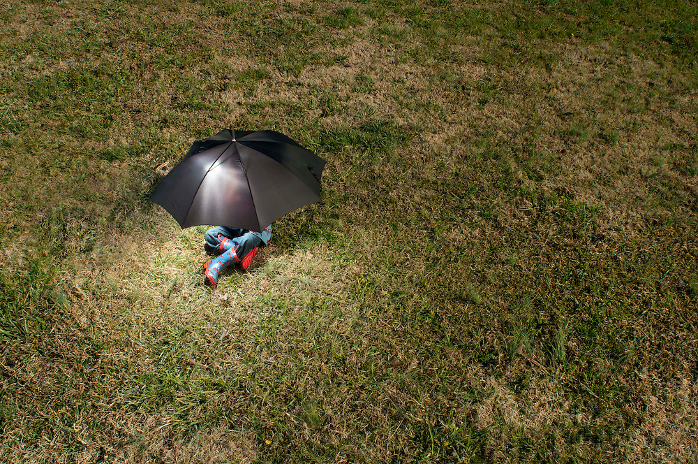 One 3-year-old boy plays with a black umbrella out in a field. He is wearing a rain coat and boots that have red tractors on them.