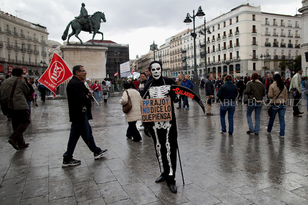 A demonstrator wearing a skeleton fancy dress holds a placard that reads 'Rajoy does not say what he thinks'. 'Wages' during a protest against the economic policies of the Spanish government during May Day in Madrid on May 1, 2012. Trade Unions CCOO and UGT have called for continues demonstrations against the severe austerity plans of the Spanish government. This month unemployment has reached a record rate and the government has announced that immigrants with no legal status will not be covered by the health public services. The government aims to get the deficit down to 5.3 percent this year and 3.0 percent in 2013.